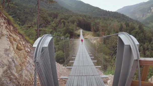 People on a suspension bridge in the mountains near the village of Perarollo di Cadore.