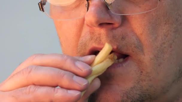 große Lippen. Mann isst Pommes.