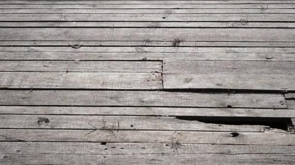 ein großes Stück Eis fällt auf den Holzboden und zerbröselt.