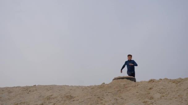 Kinder und Jugendliche vergnügen sich auf dem weißen Sand. Parkour