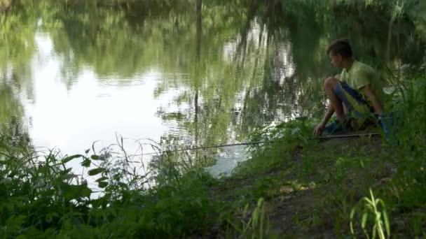 dítě v pubertě chytí rybářské tyčinky na rybníčku.
