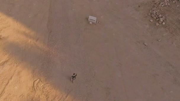 enchanted girl walks through the desert to the white piano. A strange dream. Aerial view.