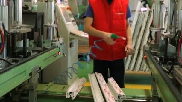 Dělníci v dílně. Řádek výroby plastových oken