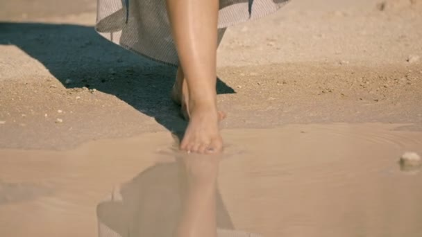 young woman cautiously enters the lake water. body part,