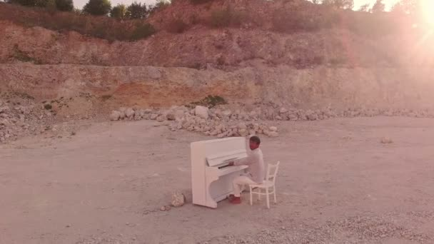 dark man plays piano in mountains among stones. Unreal story