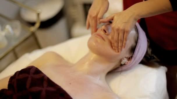 Masáž obličeje ve spa salonu krásy. Žena se těší relaxační masáž obličeje v kosmetologii lázeňském centru