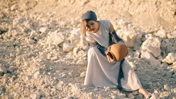girl in ethnic dress sits near the road and pours sand out of the pitcher. The water turned into sand