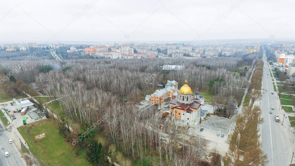 Aerial view of the autumn park, church and roads against the background of multi-storey houses