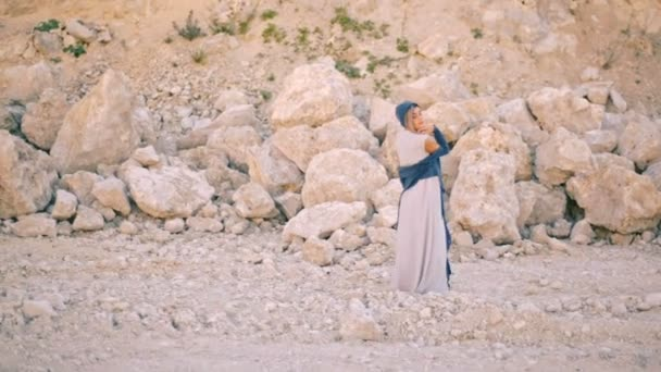Beautiful and dreamy young woman dances against a background of mountains and stones