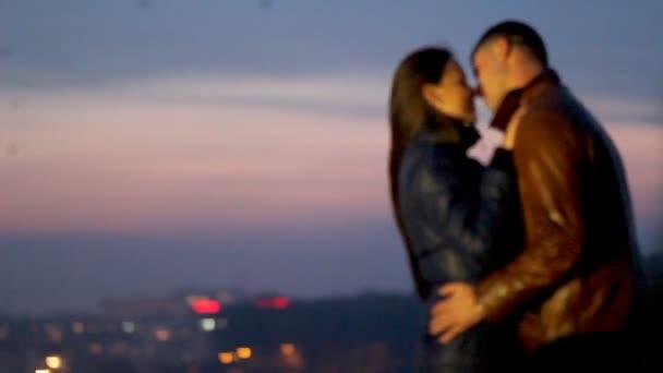 Glückliche Verliebte kuscheln vor dem Hintergrund einer nächtlichen Stadt