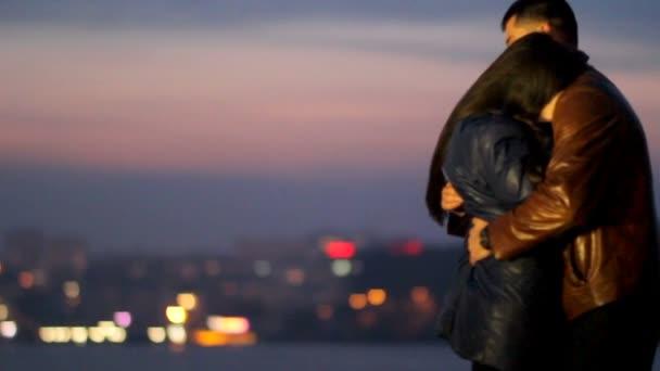 Chlap láskyplně obejme dívku na pozadí nočního města