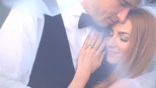 Mladý pár v lásce, něžném objetí pod závoj nevěsty. Koncept jemný a chvějící se láska
