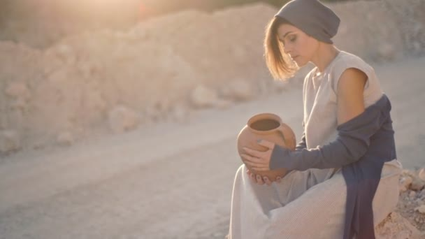 Lonely sad woman sits on the background of a sandy road and stones with an empty clay vase
