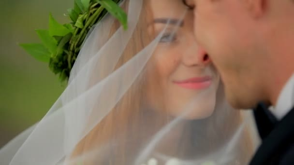 Beautiful bride under a veil and a groom on their wedding day