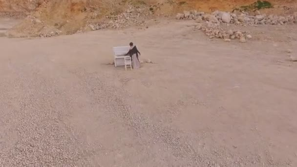 Surreal story- girl near the white piano in the desert against the background of mountains and stones. Aerial view.