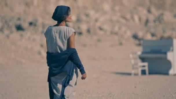 Unavený mladá žena chodí naboso na štěrku na pozadí hor a bílý klavír