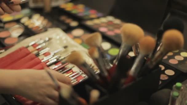 Cosmetici professionali nel salone di make-up. Lussuosi cosmetici per il make-up. Rossetto multicolore, ombre, polvere, close-up matite