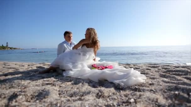 Surrealism. Bride in a gorgeous dress with the groom are on the sand by the sea