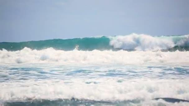 Malebné vlny Atlantského oceánu zpomalují pohyb na černé oblázkové pobřeží Tenerife