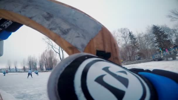 Pohled na hokejové pole z lavice. Hokejové rukavice a klacky v popředí.