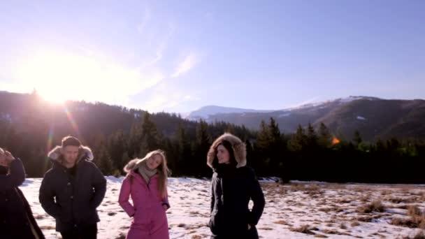 Tři dívky a chlap stojí na zasněžené louce na pozadí jehličnatého lesa a krásné hory za slunečného dne