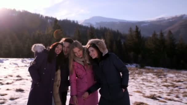 Three girls and a guy have a rest in the mountains against the background of a coniferous forest on a sunny winter day