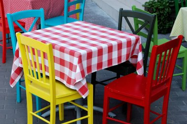 Bright and colorful table and chairs in the summer cafe.