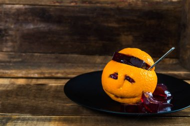 Kids Halloween Table set with Bloody Jelly, which is served inside the Orange with sad face
