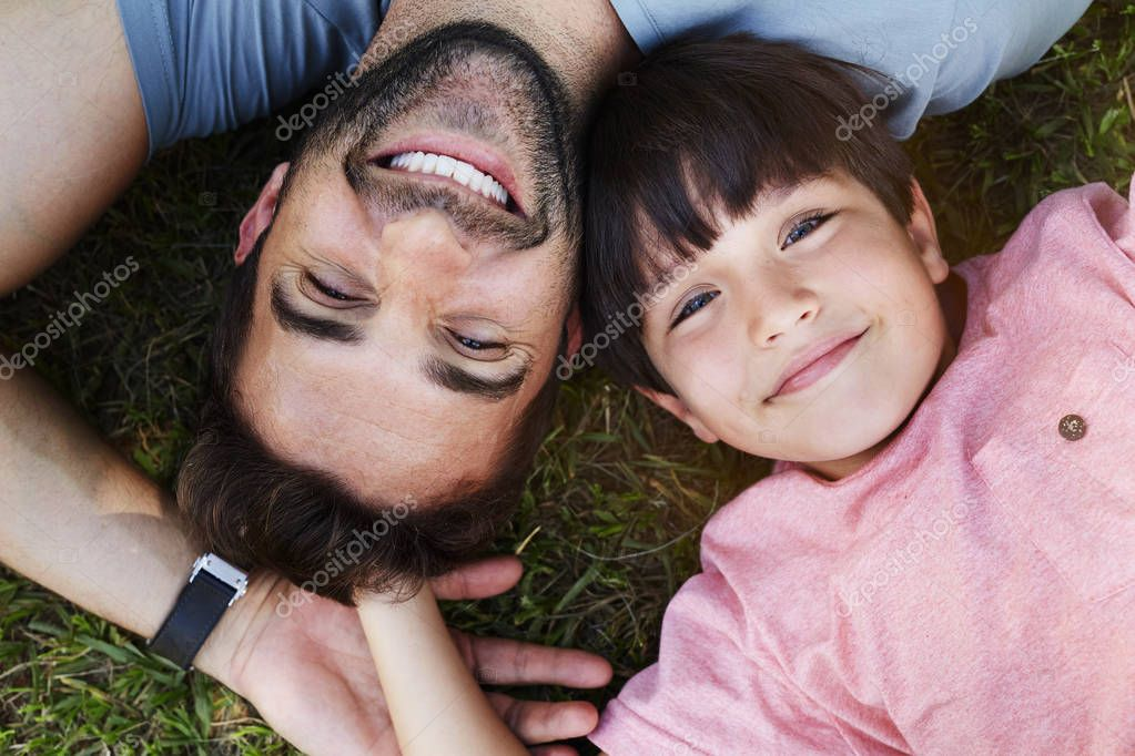 Happy dad and boy lying on grass, smiling
