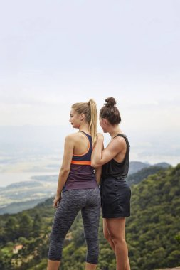 Sporty young girlfriends looking at view from high