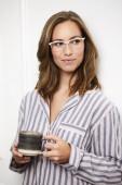 schöne Frau in Pyjama und Brille, wegschauend