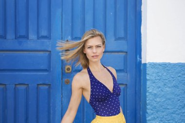 Windswept blond in blue top by door, portrait