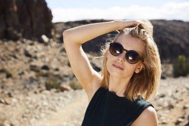 Gorgeous model wearing shades in desert, portrait