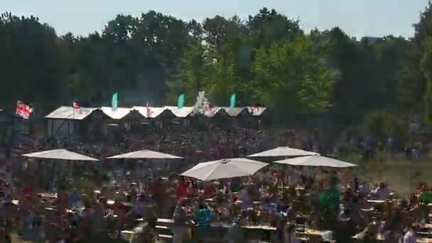 Crowd of hungry people eating meals around tables outdoor during BORZHOMI Festival on September