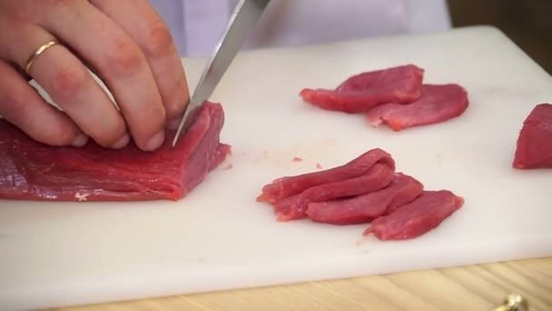 Ruce, řezání čerstvého masa, řezání masa na kuchyňské desce, řezání syrového masa