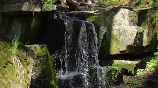nahoru úvodní blízko vodopádu closeup pramenité vody, jak to padá a kapky na zeleným mechem, zavřete záběr na velký krásný vodopád detail Vodní kapky