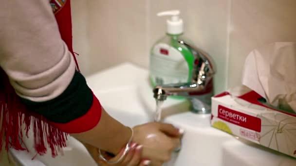 lány kezét, a lány neki mosás mosás kezet, mosdó, a közeli egyetlen kéz és a víz spray