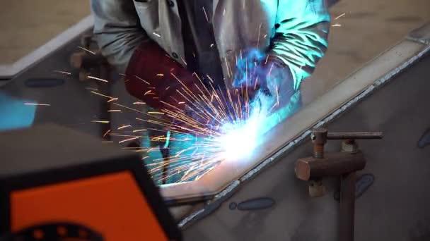 pracovník provozuje svářečské práce, Welder při práci ve výrobě, Welder sváření kov v dílně