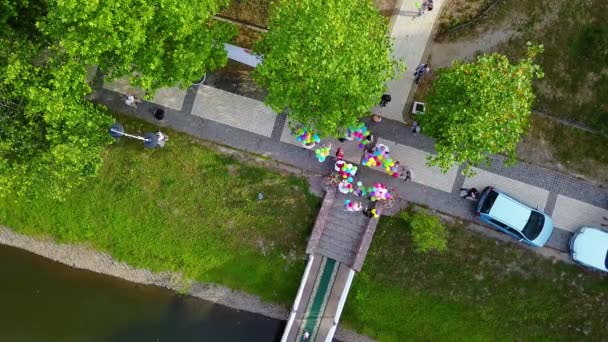 top view of people with multicolored  balloons, takeoff of multicolored balloons, Lots of balloons floating up into the sky,  festive release of colorful balloons