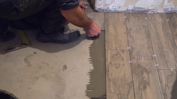Pokládka na podlahu, keramická dlažba, tlačením dolů a regulaci, instalace plastových překřížů pro upevnění, profesionální dělnice pokládání dlaždic na podlahu