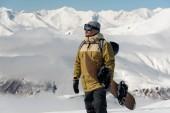 muž v lyžařské ochranné brýle a teplé barvy, s snowboard ve svých rukou, stoupne na trati proti zasněžené hory
