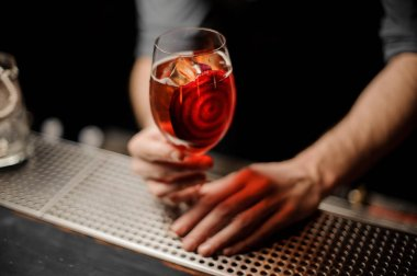 Professional bartender serving a delicious cocktail with a decor of red vegetable slice
