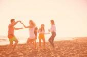 Fényképek tánc a strandon, a gyönyörű nyári sunset boldog fiatalok csoportja