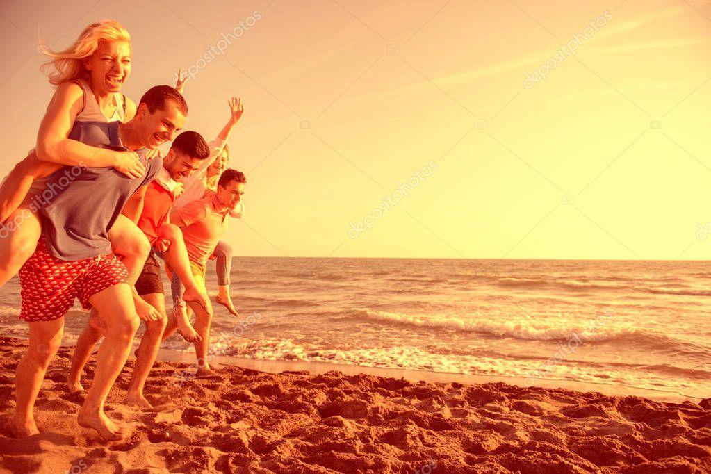 Friends fun on the beach under sunset sunlight