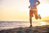 Nízké část názor člověka běží na pláži při západu slunce