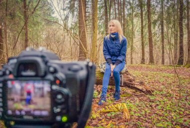 blonde girl in a blue jacket, jeans and shoes sits in the forest on a fallen tree and records a blog on camera, showing emotions of surprise, disappointment. concept of blogging, modern technologies