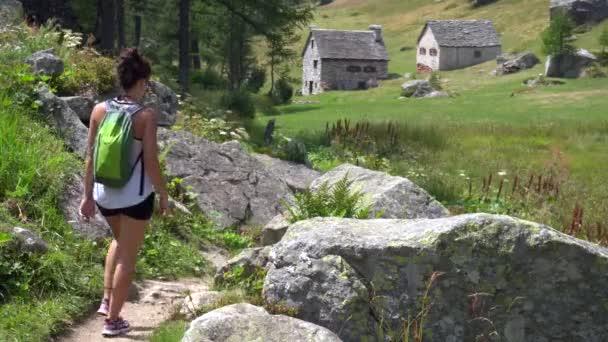 Žena kráčející horskou stezkou s útulnými domy na pozadí, Dolomity, Itálie.