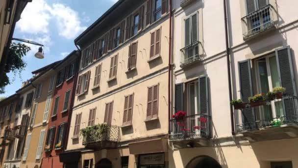 Itálie, Milán Červenec 2020 - Letecký pohled na okres Brera po ukončení uzamčení v důsledku vypuknutí koronaviru COVID-19 - typické barevné domy a turista s maskou procházky v pěší zóně