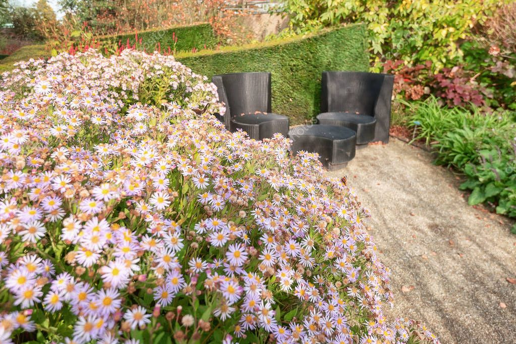 Two black design garden chairs and table next to a flowery border in a garden somewhere in The Netherlands