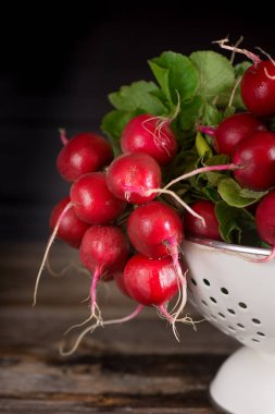 Fresh wet radishes in white colander on the an old wooden table. Village style. Dark key photo.